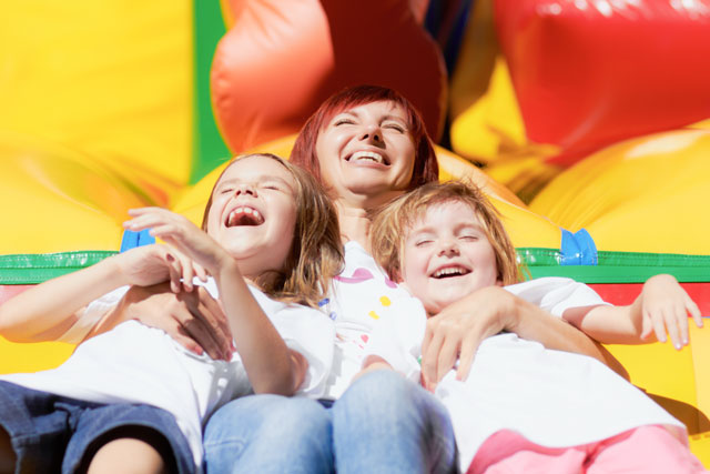 mother with kids smiling on bounce house