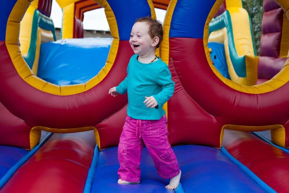 Funny laughing toddler runs on a bounce house
