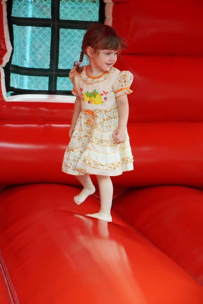 Little beautiful happy girl jumps on red bouncy castle and laughs