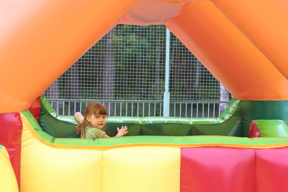 Little girl plays in colored bounce house