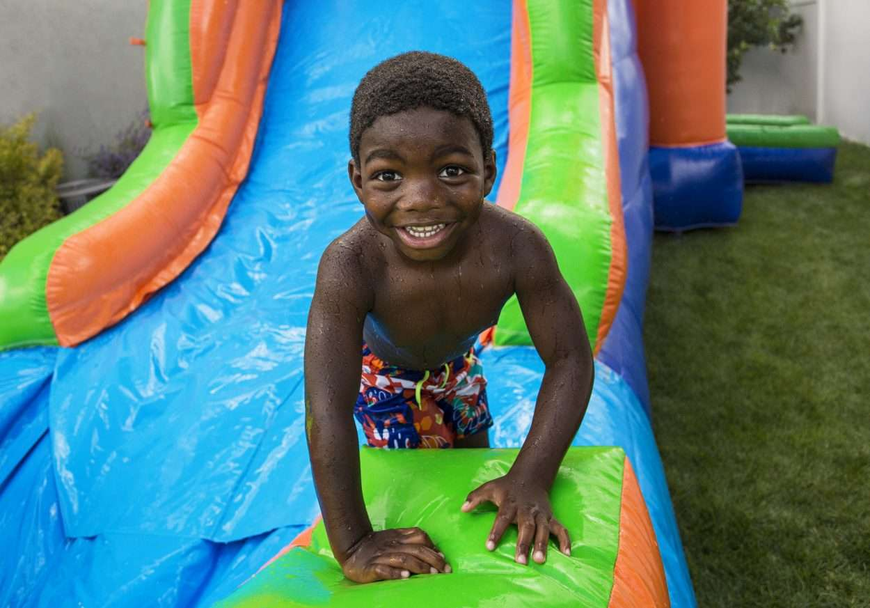 Smiling little boy sliding down an inflatable water slide rental in Miami